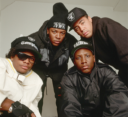 ca. 1990 --- Portrait of members of the rap group, NWA, including DJ Yella, MC Ren, Eazy-E (left, wearing straitjacket), and Dr. Dre (center, wearing ski cap). --- Image by © CORBIS