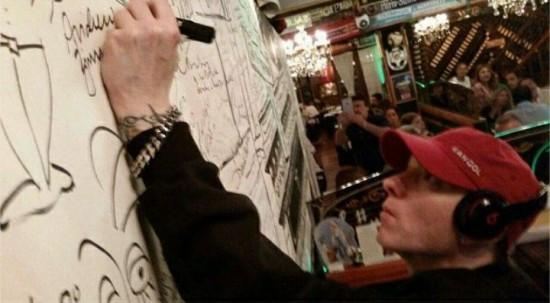 Eminem оставляет свой автограф на стене автографов одного из баров в Буэнос-Айрес