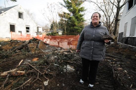 Девушка берёт кирпич из руин дома детства Эминема