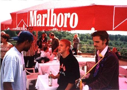 "Em: «Эй, Пруф. Все люди в этом кафе пялятся на меня. И что это за чувак с гитарой?» / Em: "" Yo Proof, don't look now but all the Marlboro people are staring at me. And who is that dude with the guitar?"""